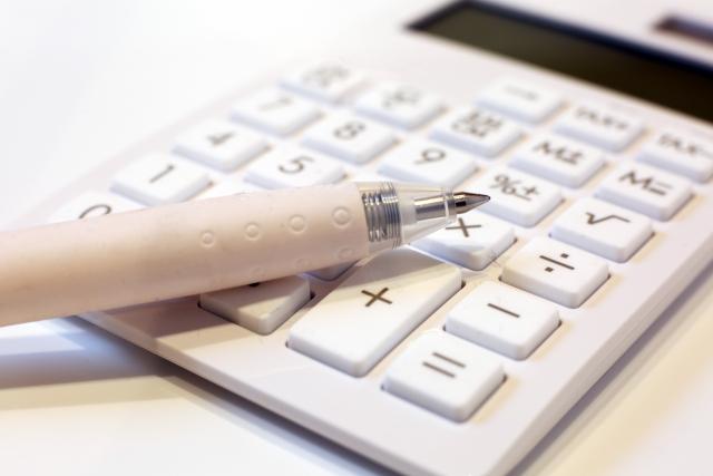 机の上に置かれた電卓とペン